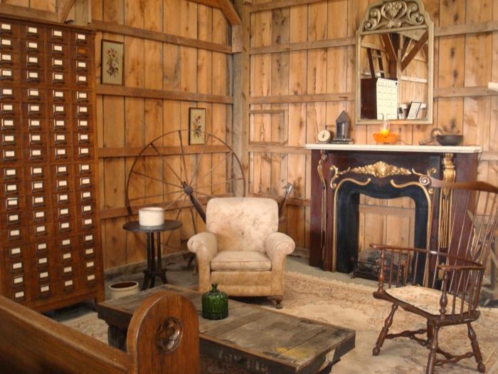 como decorar un salon, salon rustico con chimenea y espejo, paredes de madera, rueda y sillón