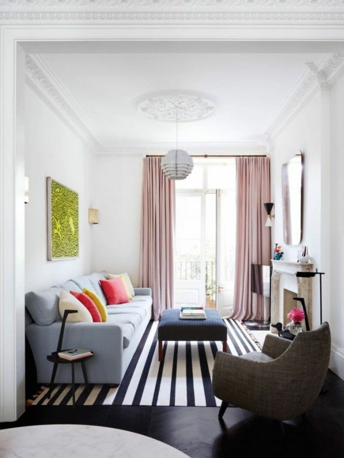 salon, salón estrecho con ventanal y cortinas rosadas, tapete rayado, sofá azul con cojines y chimenea