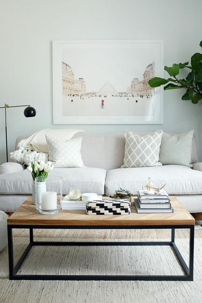 salon, sofá beige y mesa rectangular de madera con tulipanes, cuadro con Louvre y planta verde