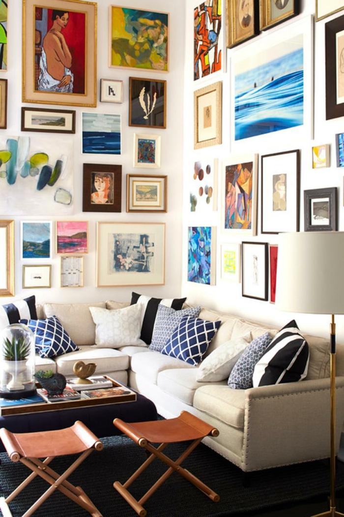 salon, paredes llenas de cuadros, sofá en forma L con cojines en tonos azules, dos sillas plegables y mesa