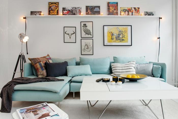 salon, sofá azul en forma de L y cojines, mesa cuadrada blanca de plástico, bombillas encentdidas y cuadros con animales y bicicleta retro