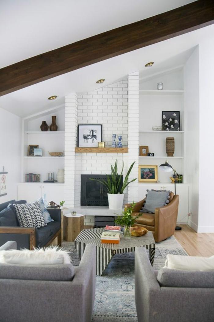 salon, techo inclinado, salón con tres sillones y mesa rayada, chimenea de ladrillo blanco y planta verde