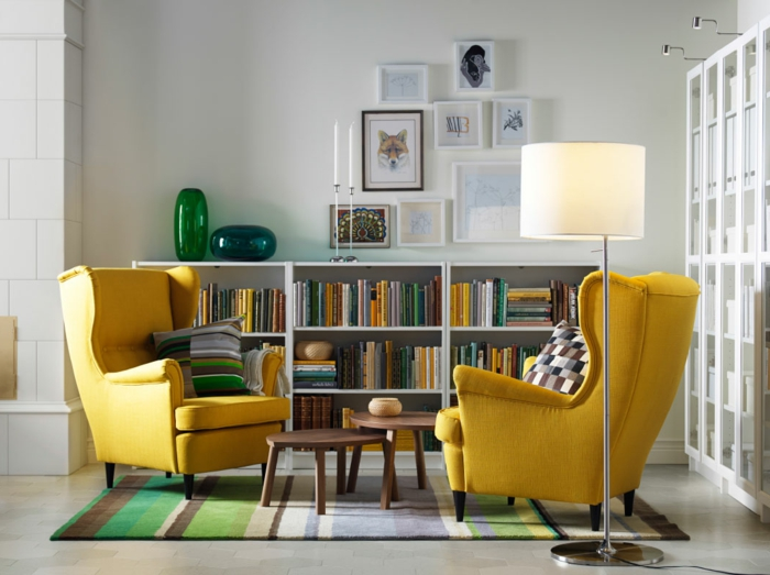 decoracion salones modernos, salón con dos sillones amarillos iguales, tapete rayado en verde y marrón y librería