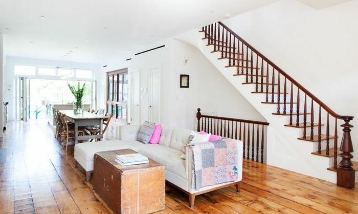 decoracion salones modernos, salón abierto con comedor, escaleras grandes, sofá blanca con cojines rosa, mesa de caja antigua
