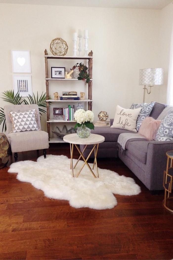 decoracion salones modernos, salón en colores pastel, tapete de piel, mesita redonda con flores y estantería de amdera