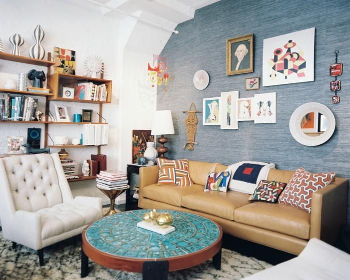 decoracion salones modernos, salón con pared azul, sofá de piel, mesa azul redonda, etsantería con libros