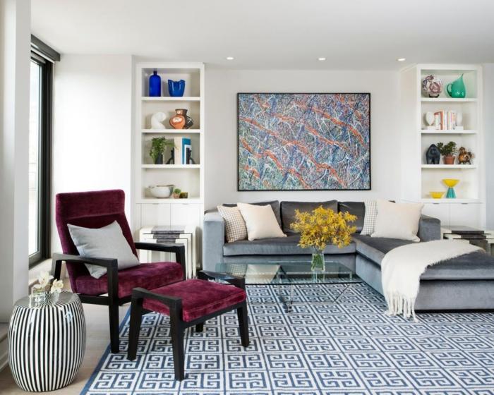 decoracion salones modernos, salón con silla cama de terciopelo púrpura, sofá gris con cojines. estanterías blancas simétricas y cuadro