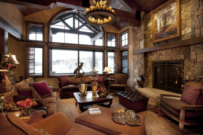 salones rusticos, salon con chimenea de piedra, lámpara con candelas, alfombra y dos sofás con cojines
