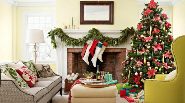 arbol de navidad original, decorado con grandes flores navideños rojos y juguetes de diferente forma, cojones con motivos navideños, guirnalda verde en la chimenea