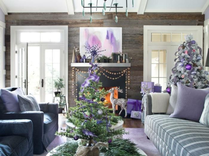 arbol de navidad original, salón decorado en color lila y blanco, grandes sofás y chimenea acogedor, dos árboles de navidad