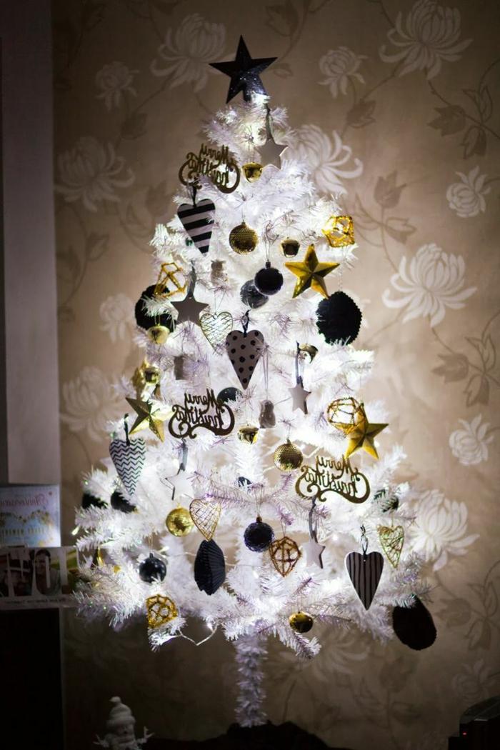 arbol de navidad original muy relumbrante, con adornos en blanco dorado y negro , tapices de papel con flores