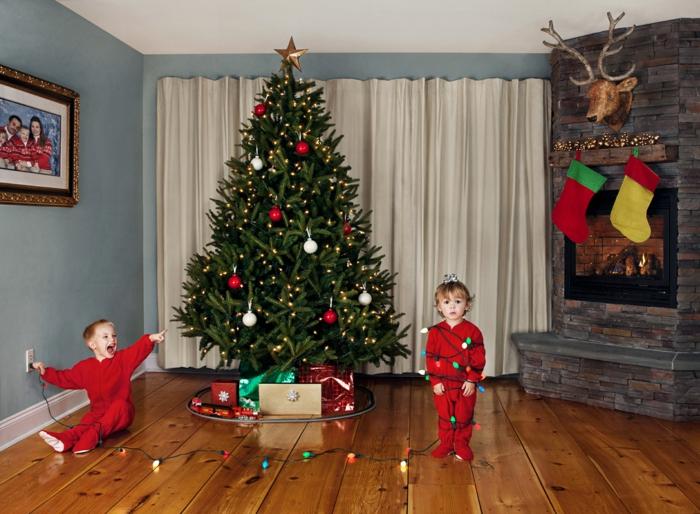 arboles de navidad decorados, pino grande vivo decorado con esferas en blanco y rojo y lamparillas en amarillo, chimenea acogedora