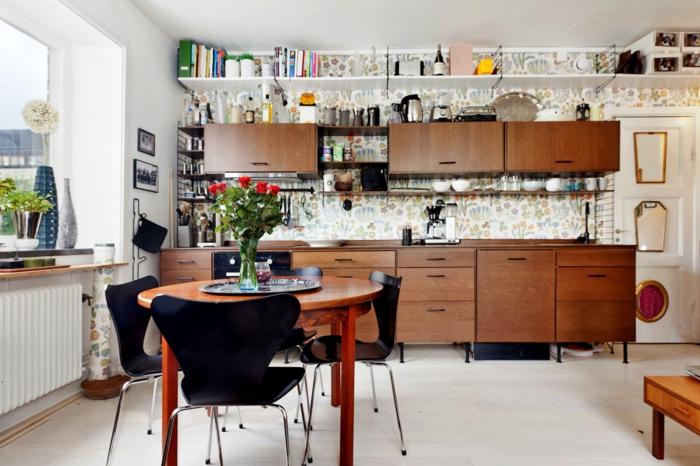 cocina comedor, cocina abierta a la sala de estar, muchos armarios de madera, pared con tapiz de papel, sillas negras con mesa de madera redonda