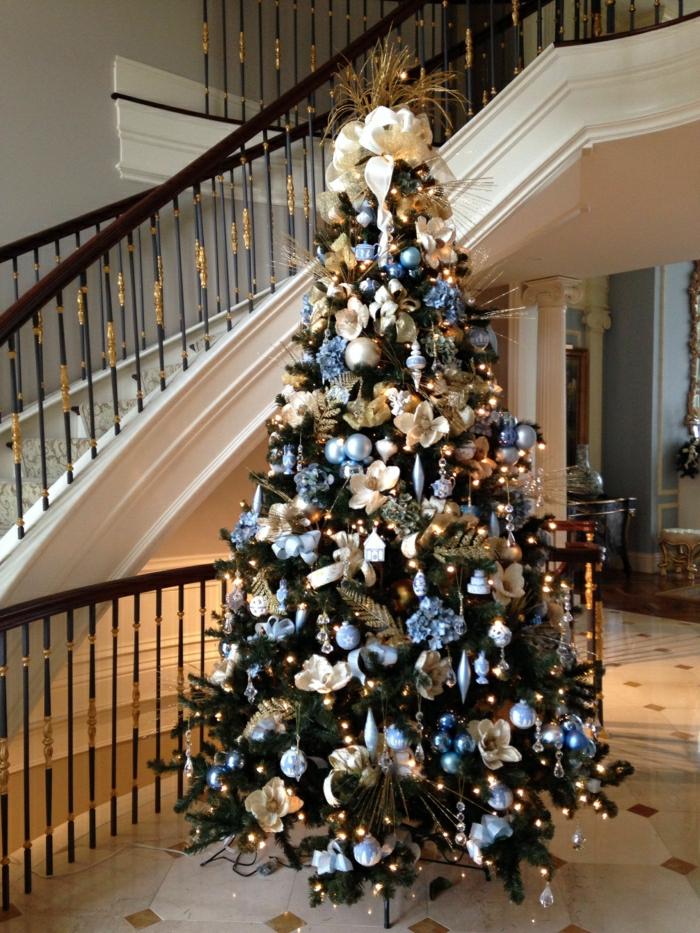 arboles de navidad originales, ornamentos para el árbol en colores pastel, decoración con elementos florales, árbol colocado al lado de la escalera