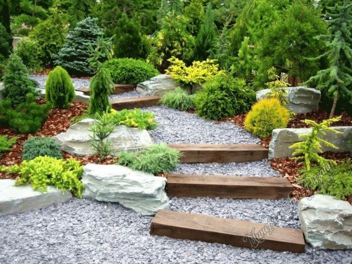 jardines pequeños, escaleras de palos de madera, suelo con pavimento de piedras pequeñas, arbustos pequeños con pinos altos