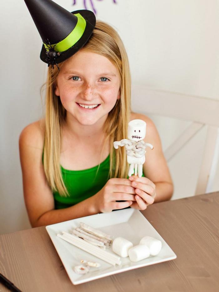 decoracion halloween, pequeña chica con sombrero de bruja en negro y verde y araña decorativa, juguetes decorativos de malvaviscos
