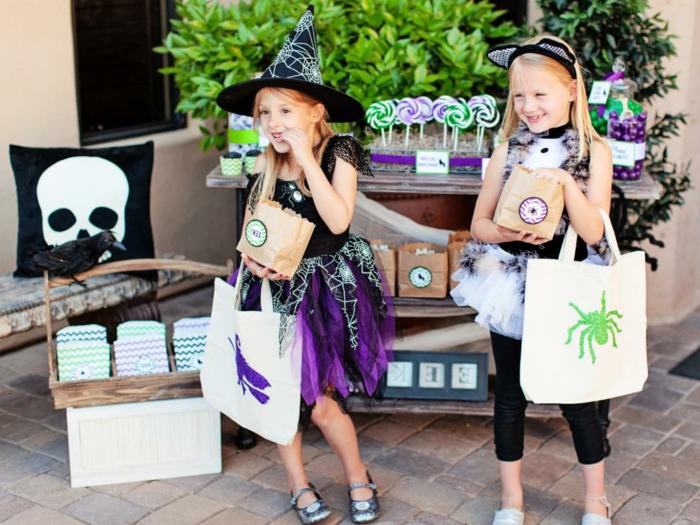 decoracion halloween, dos niñas con disfraces y accesorios con los motivos de halloween, chupa chups en espiralas coloridas