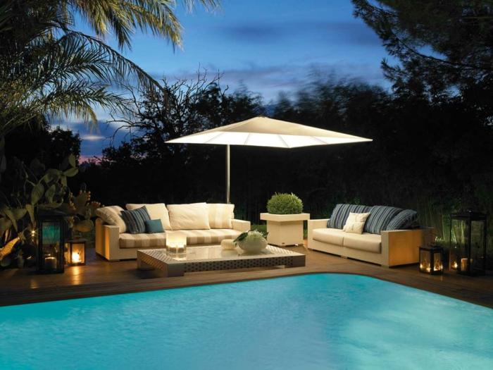 diseño de jardines moderno, grande piscina y muebles en el patio, sombrilla con lámpara empotrada, sofás beige