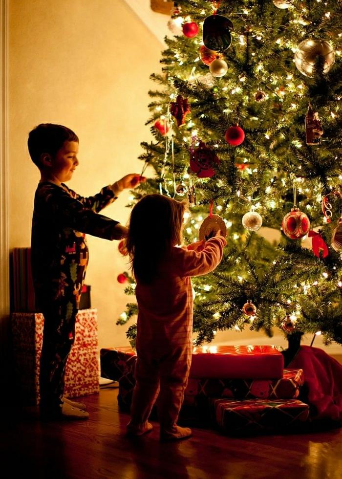 arbol de navidad decorado, pino grande con decoración en los colores clásicos para navidad, niños colocando los adornos