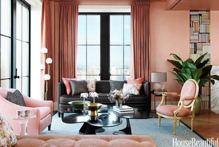cotrinas de salon den color salmón, largas cortinas de satín, muebles en rosado, estantes empotradas para libros y mesa de forma moderna