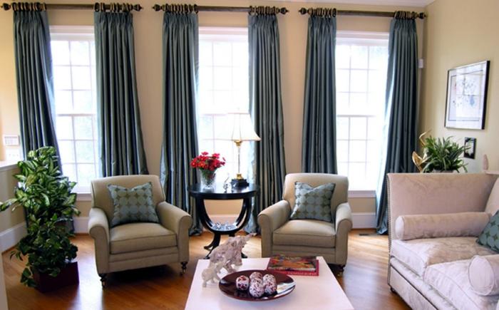 cortinas salon colgadas en anillas, barras de madera redondas, cortinas largas color azul metálico, sala de estar grande con sofás