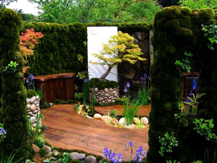 jardines modernos, pequeña plataforma con seto vivo y estrado de madera, pequeño alpineum en el medio, árboles de colores
