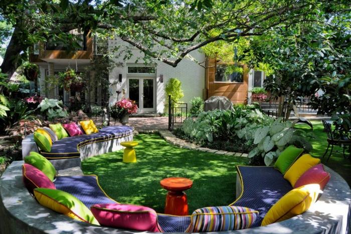decoracion de jardines, hermoso ejemplo de patio con lugar separado para descanso, construcción de piedra con cojines coloridos