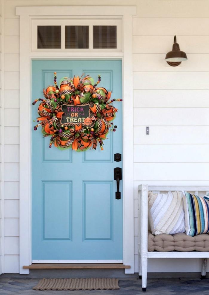 cosas de halloween, corona de halloween en colores, truco o trato, puerta en color azul claro, veranda blanca