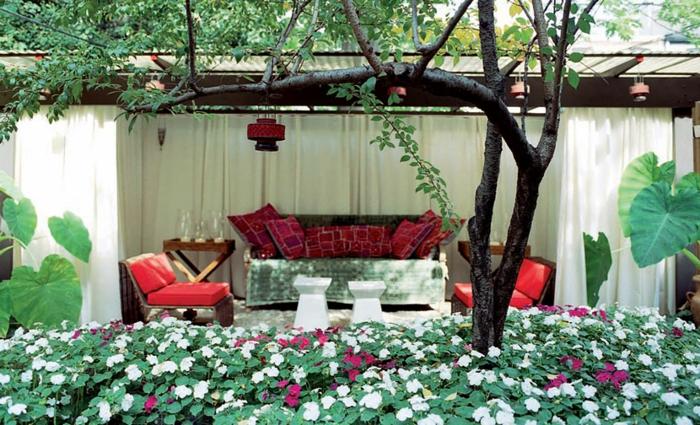 jardines con piedras, veranda original con muebles sacados fuera, colchonetas y cojines en rojo, muchas plantas con flores blancos