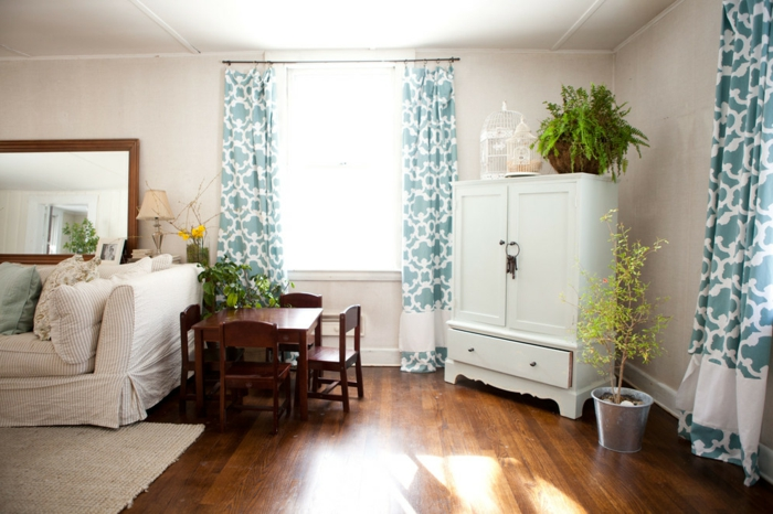 cortines modernas en tonos claros y estampados geométricos, salon con suelo de madera, grande espejo y paredes blancos