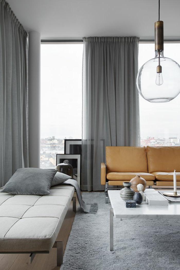 cortinas de salon, cortinas gruesas con visillo en gris, salón funcional, lámpara moderna de bombilla, objetos decorativos en la mesa
