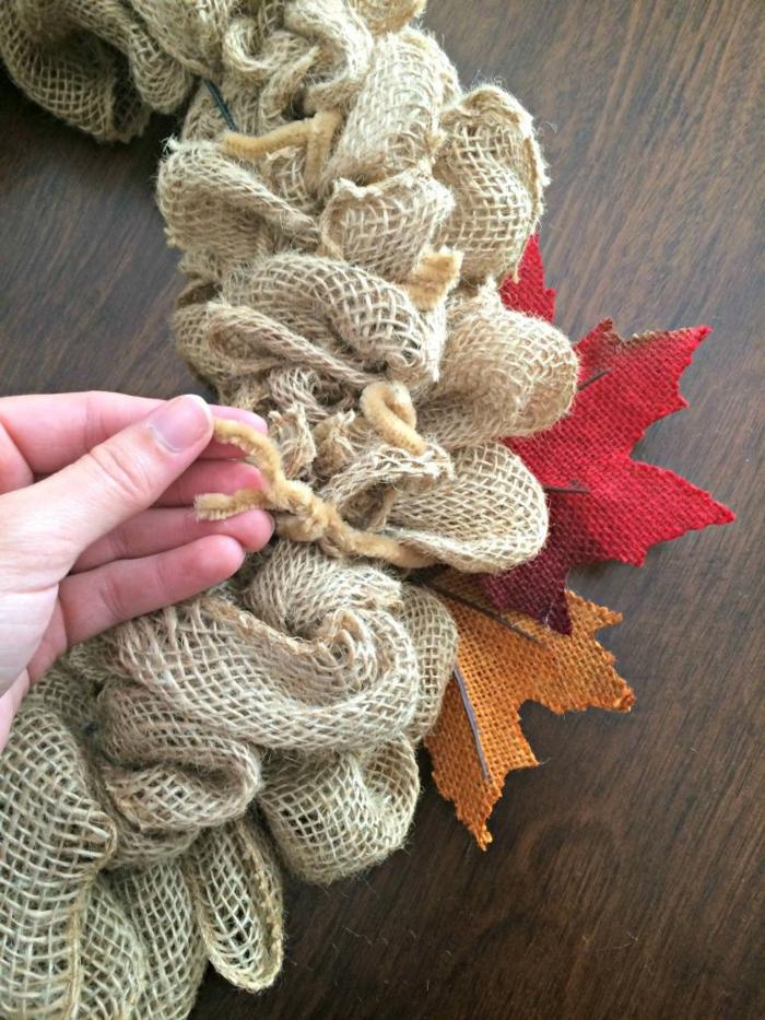 manualidades navidad, corona navideña de arpillera, limpiadores de pipa y hojas otoñales de tela, mano de mujer