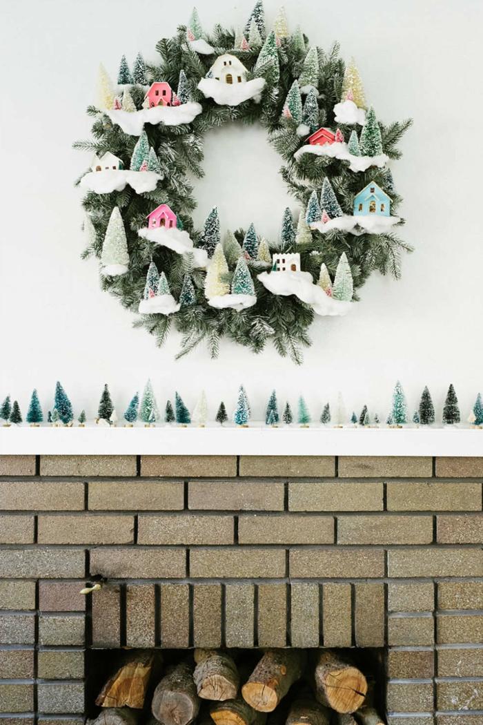 muerdago navidad, decoracion con chimenea y corona navideña verde con nieve y escarcha, casitas de color