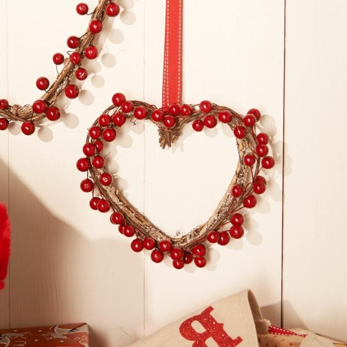 muerdago navidad, corona de navidad en forma de corazos de ramas secas y bayas rojas con cinta