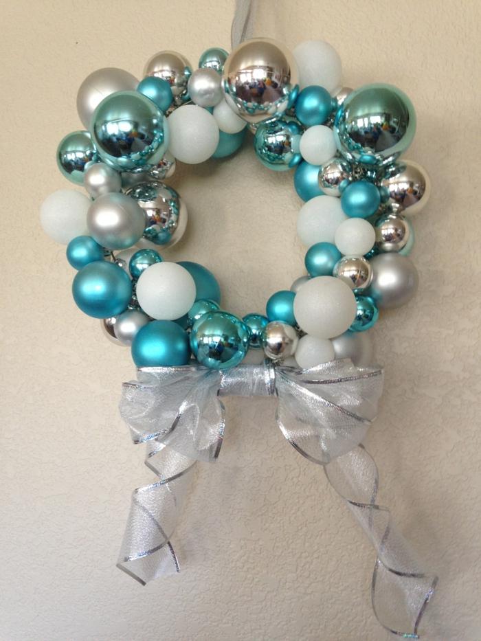 muerdago navidad, corona de navidad de bolas decorativas en plateado, azul y blanco, lazo de cinta decorativa