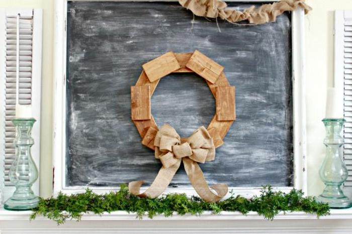muerdago navidad, corona de navidad con trozos de madera y lazo de tela de arpillera, pizarra negra