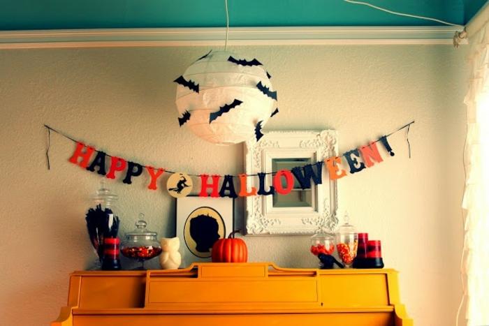 manualidades caseros, decoración hecha a mano, figuras de murciélagos, guirnalda colorida, armario anaranjado, adornos en rojo y negro