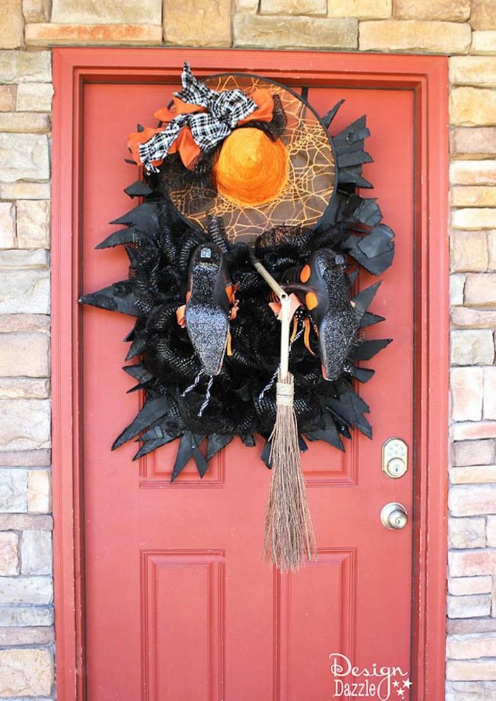 manualidades caseras, guirnalda escalofriante para tu entrada, decoración en blanco y color naranja, escoba vieja y zapatos negros