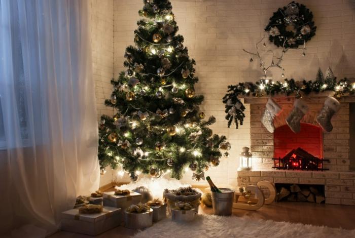 arboles de navidad decorados, interior muy bonito y mágico con lamparas amarillas y guirnaldas en la chimenea, cortinas blancas transparentes