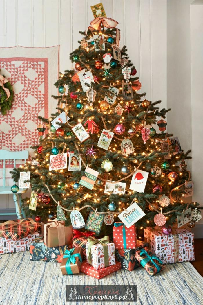 como hacer un arbol de navidad, decoracion casera de tarjetas y dibujos colgados en el pino, bolas brillantes en diferentes colores
