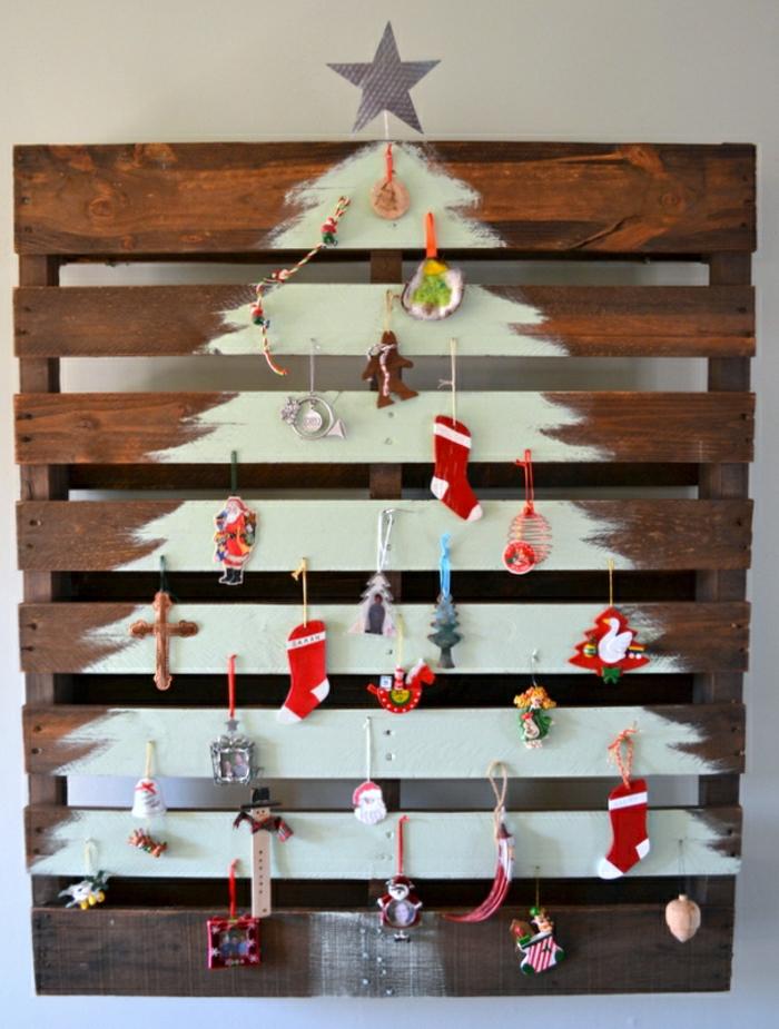 como hacer un arbol de navidad dibujándolo en madera, pequeños ornamentos de encanto colgados en clavos