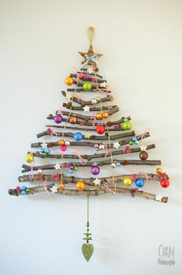 como decorar un árbol de navidad, árbol casero hecho de palos de madera, colgado en la pares, con pequeñas bolas en diferentes colores