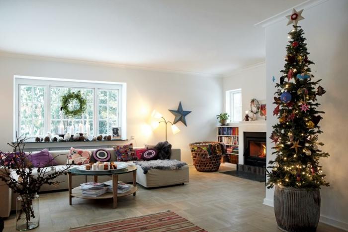 decorar árbol de navidad, árbol alto de poca anchura, salón grande decorado de cojines, grande ventana decorada con corona de navidad