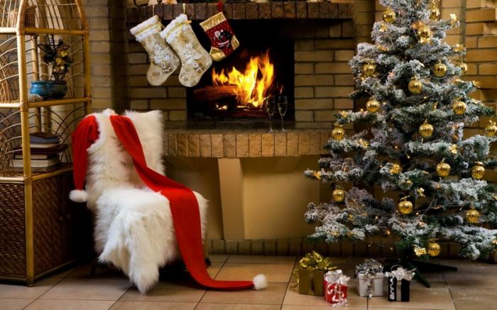 decorar arbol de navidad, pino artificial con efecto nevado, bolas doradas como decoración, calcetines navideños colgados en la chimenea