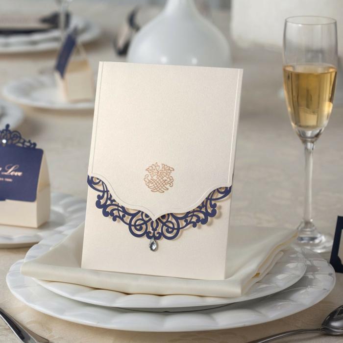 invitaciones creativas, invitación elegante en dorado y azul sobre mesa con vaso de champaña