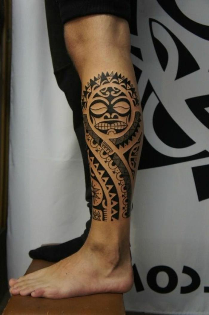 tatuajes maories, tatuaje en pierna inferior de hombre, motivos polinesios con cabeza Tiki y dientes de tiburón