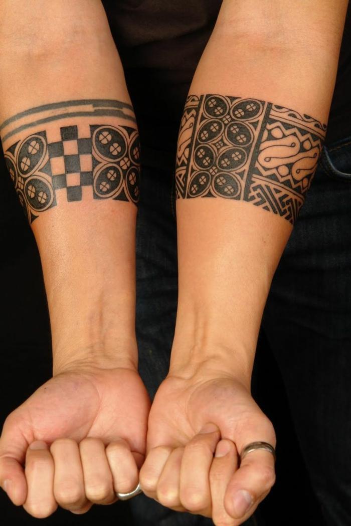 tatuajes maories, brazaletes maories en antebrazo, tablero de ajedrez, dedos con anillos