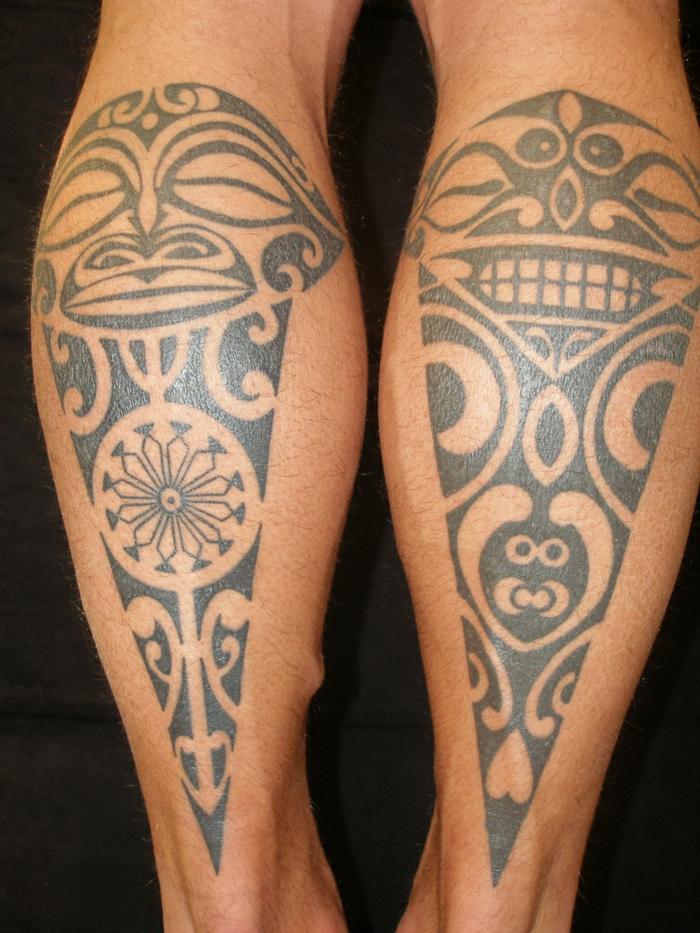 tatuajes maories, tatuaje con motivos polinesios en pantorillas de hombre, caras mitológicas