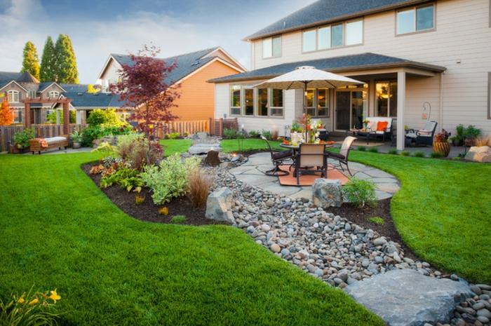 casa y jardin, casa con doble fachada, espacio decorado con piedras, rincón con comedor