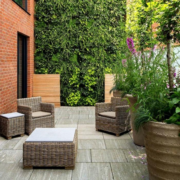 jardines modernos, muebles simples de mimbre, macetas masivas con plantas salvajes, plantas trepadoras en la pared entera